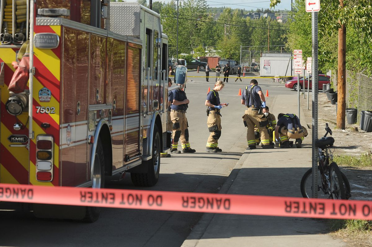 The Anchorage Fire Department hazardous materials team tests a white powder spread alongside Karluk Street between Third and Fourth avenues near Bean's Cafe and Brother Francis Shelter in Anchorage on Thursday. (Bob Hallinen / ADN)