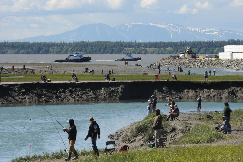 Tug boats pass by the mouth of Ship Creek as anglers fish for king salmon during an outgoing tide on Sunday, June 14, 2020. (Bill Roth / ADN)