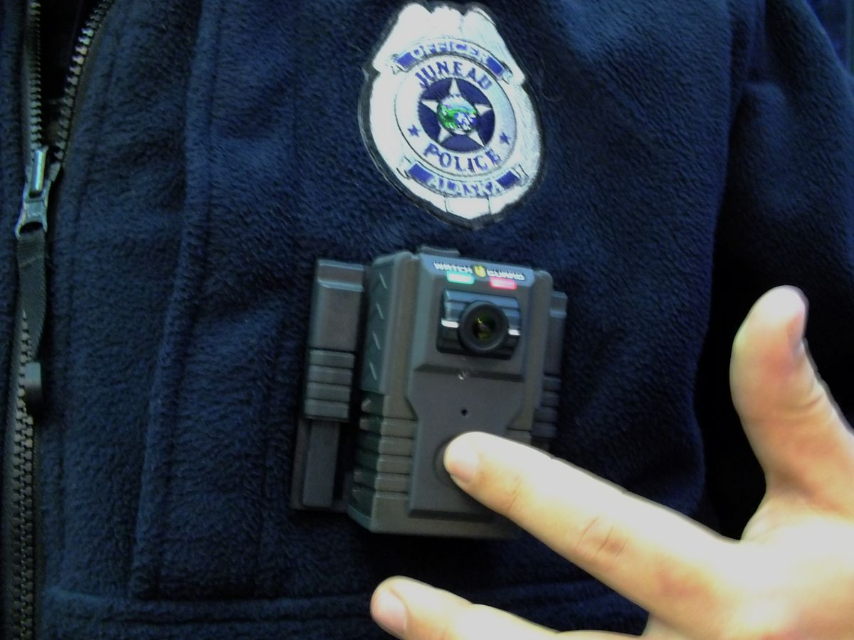 The green light on this body camera indicates that it is on and recording a continuous loop. When an officer presses the button below the lens and the red light comes on, then the recording is being stored and tagged. (Matt Miller / KTOO)