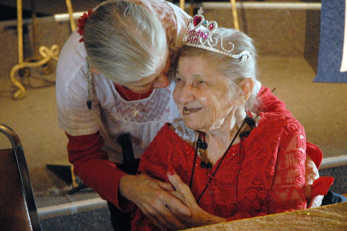 Charlotte Schwid gets a hug from friend Rose Galler during Schwid's 100th birthday party at the Eagle River VFW on Wednesday, May 22, 2019. Schwid is a former Army nurse who served in England during the Allied invasion of Europe in World War II. (Matt Tunseth / Chugiak-Eagle River Star)