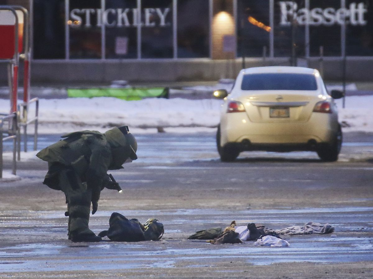 A man investigates items that a robot removed from a bag in a vehicle in the parking lot east of the Midtown Mall in Anchorage on Monday, Jan. 11, 2021. The surrounding area and roads remained closed until roughly 5 p.m. that night. (Emily Mesner / ADN)