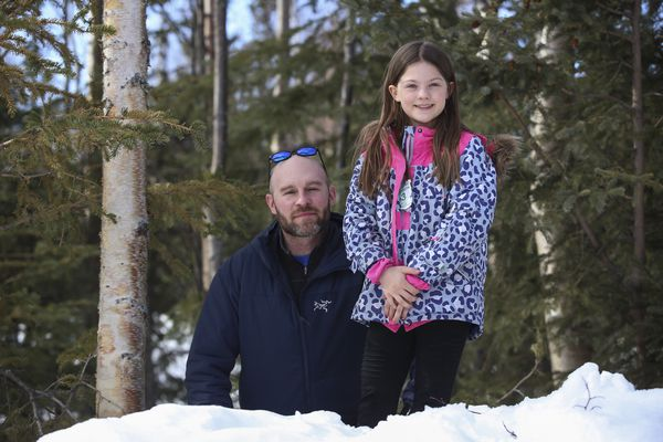 Michael Cipriano stands with his daughter, Abigail, 9, on a mound of snow near where she and her sister were playing when they encountered a lynx in the front yard of their Anchorage home. Photographed on Friday, April 2, 2021. (Emily Mesner / ADN)