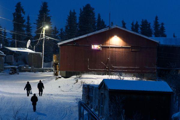 Pedestrians walk from the Noorvik Native Store on December 4, 2018. (Marc Lester / ADN)