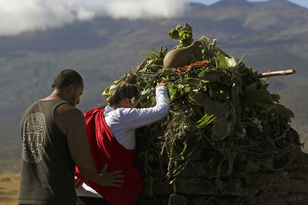 FILE - In this Sunday, July 14, 2019, file photo, Native Hawaiian activists pray at the base of Hawaii's Mauna Kea, background. For activists who say they're protecting Mauna Kea, the fight against the proposed Thirty Meter Telescope is a boiling point in Hawaiian history: the overthrow on the Hawaiian kingdom, battles over land, water and development and questions about how the islands should be governed. (AP Photo/Caleb Jones, File)