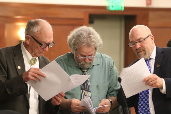 Three Fairbanks members of the Alaska House peruse documents during a break from their floor session Saturday, May 12, 2018 at the Alaska Capitol in Juneau. From left, Republican Steve Thompson, Democrat David Guttenberg and Democrat Adam Wool. (Nathaniel Herz / ADN)
