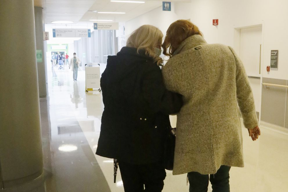 Janine Blezien, left, and Dianne Green walk arm-in-arm at Rush University Medical Center in Chicago on Wednesday, March 17, 2021, during their first in-person meeting. Blezien, a nurse at Rush, and Green, a retiree, met by phone the previous year through the hospital's 'friendly caller ' program for which Blezien is a volunteer. They were able to get together after being vaccinated against COVID-19, and they plan to go out to a restaurant and shop together, once they both feel safe doing so. (AP Photo/Martha Irvine)