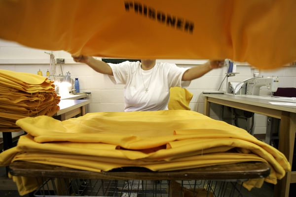 Michelle Gates stacks prison garments after sewing on sleeves and collars Thursday, July 21, 2005 morning at Hiland Mountain Correctional Institution. (Daron Dean/Anchorage Daily News)