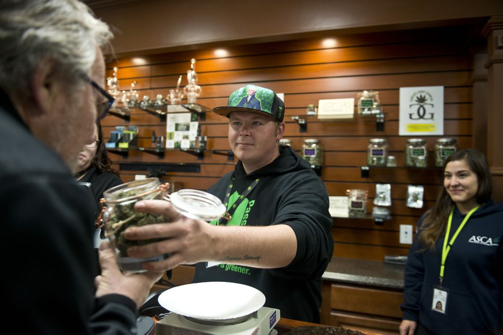 Michael Holcomb smells a jar of marijuana held by Herbal Outfitters general manager Derek Morris in Valdez on .Oct. 29, 2016. (Marc Lester / Alaska Dispatch News)