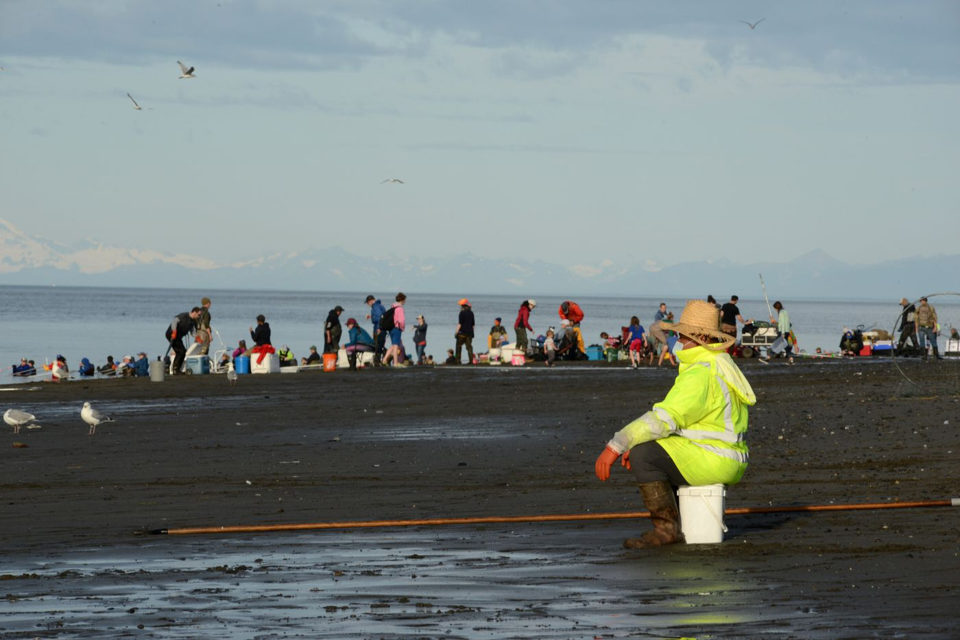 A person with a mask waits for more fishing action on the Kenai River beach on Tuesday. (Anne Raup / ADN)