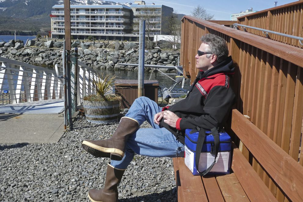 Alaska Gov. Mike Dunleavy sits beside a case containing COVID-19 vaccine doses as he waits near a floatplane dock on Thursday, April 22, 2021, in Ketchikan, Alaska. State health officials have said Alaska has an ample supply of COVID-19 vaccines, and Dunleavy, who flew from Ketchikan to Hyder, Alaska, said he wanted to offer vaccines not only to residents of Hyder but also to Canadians across the border from Hyder in Stewart, British Columbia. (AP Photo/Becky Bohrer)