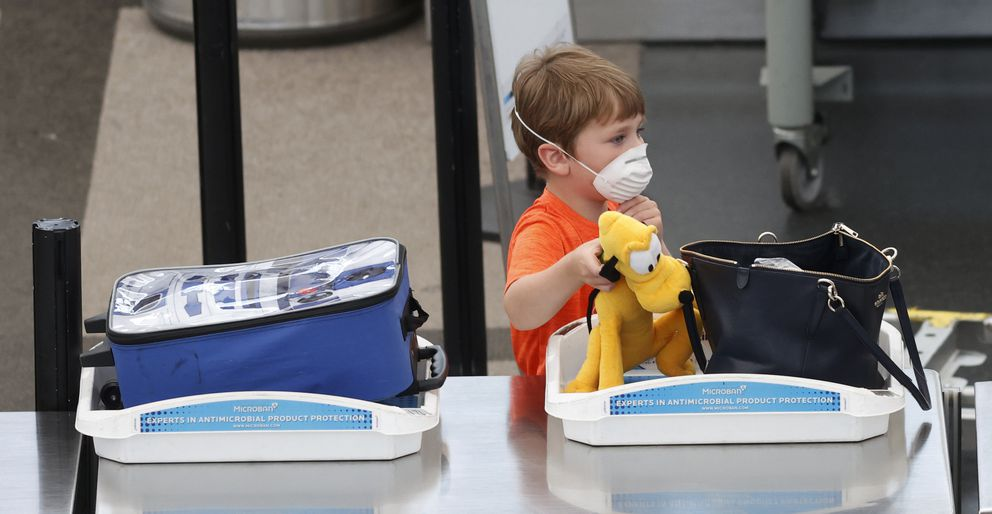 A young traveller loads his doll into a bin at the security checkpoint in the main terminal of Denver International Airport as business returns with the easing of restrictions to check the spread of the new coronavirus Wednesday, May 13, 2020, in Denver. (AP Photo/David Zalubowski)