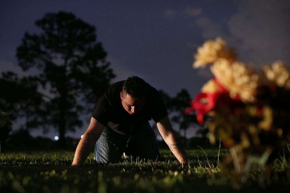 Corey Ott leans over the patch of grass where his toddler son Rylan Ott is buried inside Grand View Memorial Park. (Rick Loomis/Los Angeles Times/TNS)