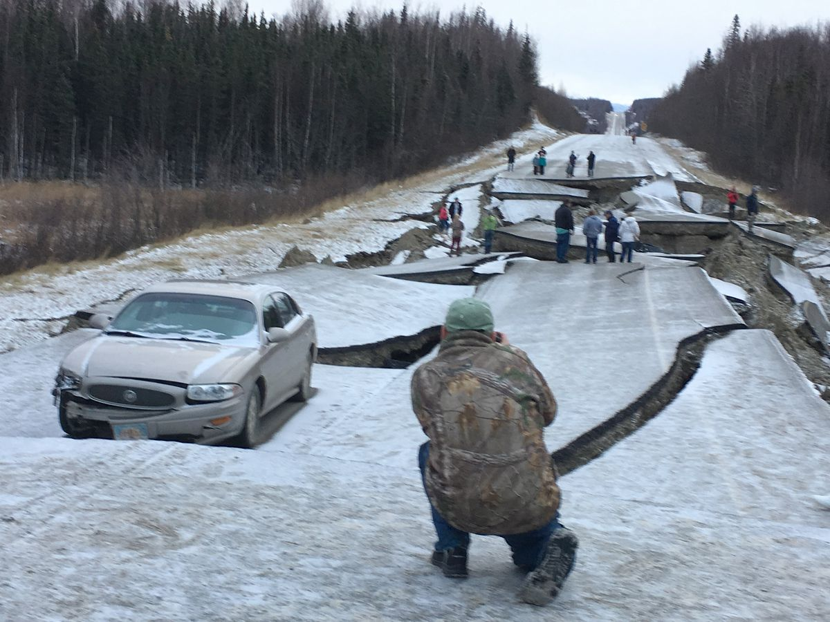 People check out Joe Fedewa's 2000 Buick LeSabre amid broken asphalt on Vine Road in the Matanuska Valley on Friday, Nov. 30, 2018. He was northbound in the dark when the 7.0 earthquake hit. (Photo by Joe Fedewa)