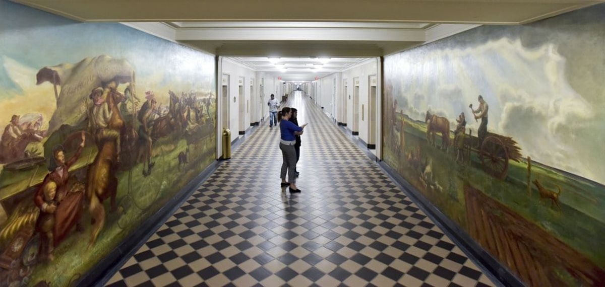 Two murals on the walls outside the Bureau of Land Management at the Interior Department in Washington. (Doug Kapustin for The Washington Post)