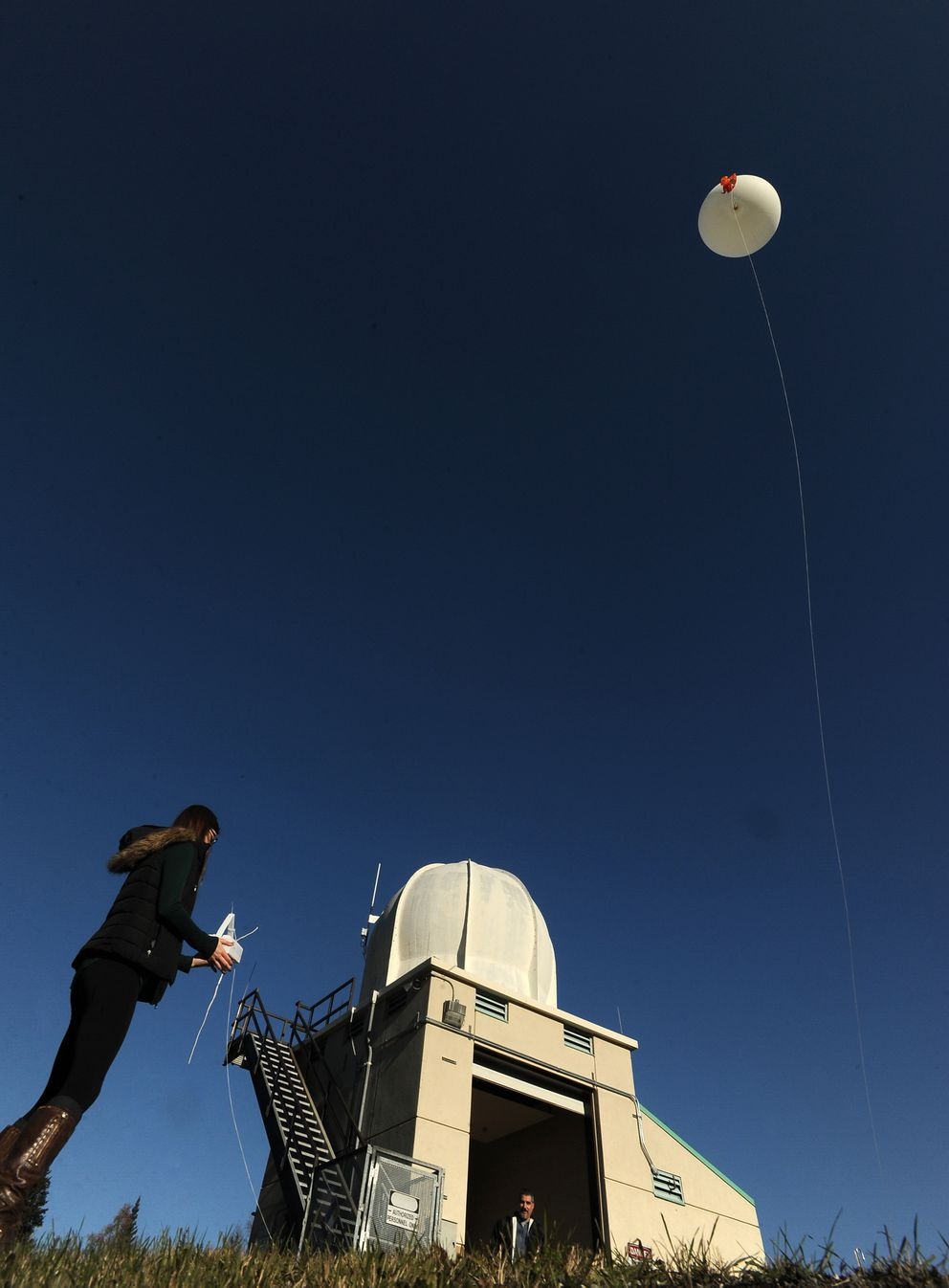 Rebecca Duel, meteorologist at the Anchorage Forecast Office of the National Weather Service, launches a weather balloon at the center in Anchorage, Alaska, on Friday, October 7, 2016. (Bob Hallinen / Alaska Dispatch News)