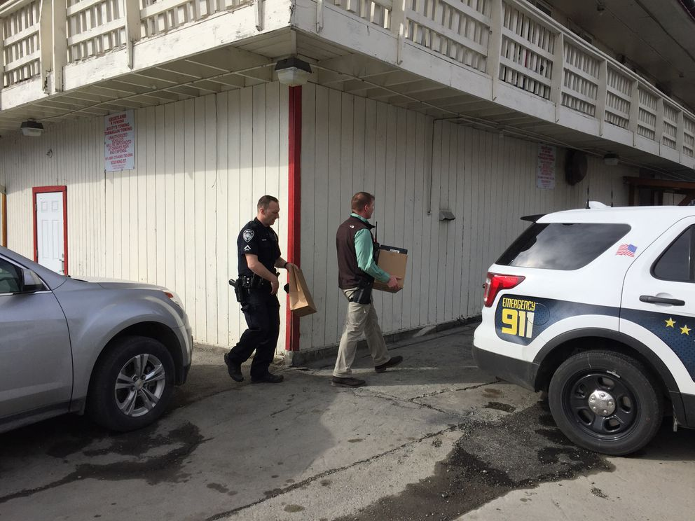 After spending about 90 minutes inside Bret Maness' apartmenton April 26, APD officers and federal agents emerged with a box and paper bag, which they loaded into the back of an APD vehicle. (Matt Tunseth / Alaska Star)