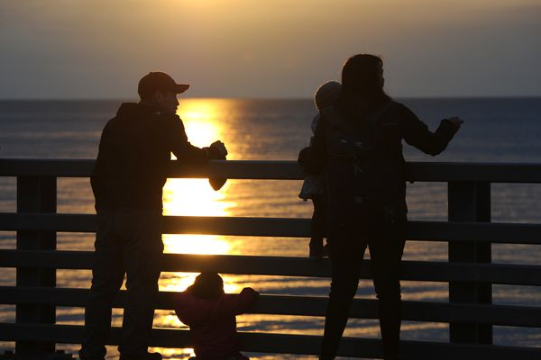 Wayne Johnson and his fiancé Catherine Ivanoff view the sunset with their children Lilly, 1, and Rosa, 3, in Kotzebue on Monday, Sept. 17, 2018. (Bill Roth / ADN)