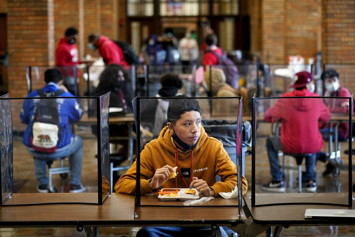 Freshman Hugo Bautista eats lunch separated from classmates by plastic dividers at Wyandotte County High School in Kansas City, Kan., on the first day of in-person learning Wednesday, March 31, 2021. The district was one of the last in the state to return to the classroom after going virtual due to the COVID-19 pandemic. (AP Photo/Charlie Riedel)