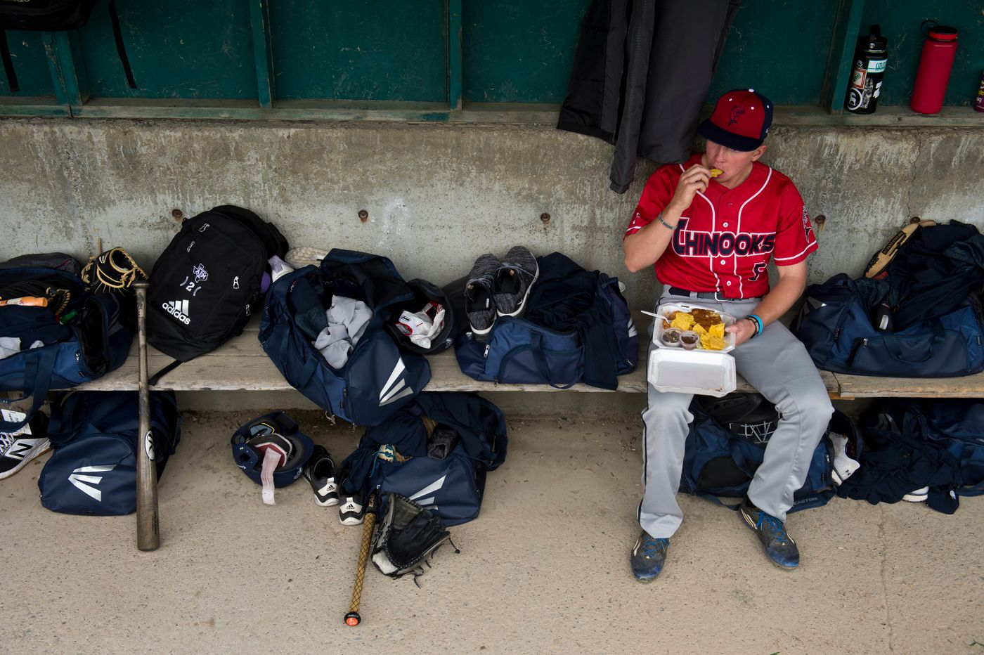 Chinook's infielder Paddy McKermitt eats in his team's dugout about an hour before game time. (Marc Lester / ADN)
