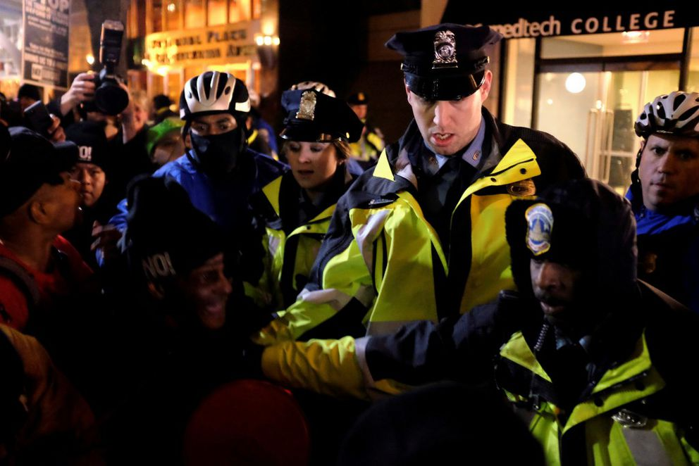 """Police officers react as demonstrators against President-elect Donald Trump knock a police motorcycle on its side outside the National Press Building while the """"Deploraball"""" wasunderway in Washingtonon Thursday. (James Lawler Duggan / Reuters)"""