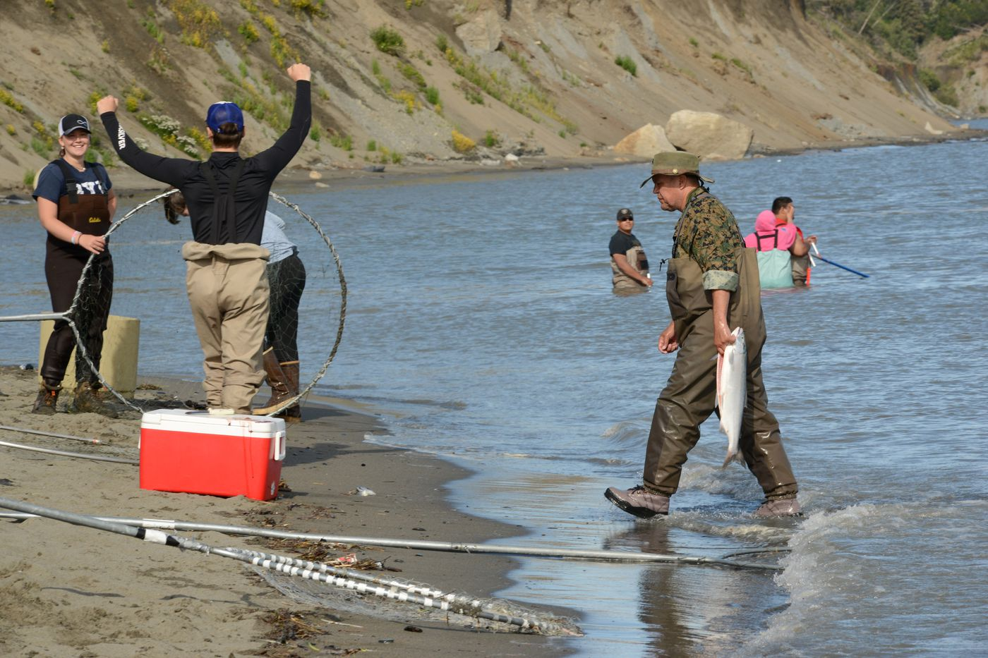A fisherman brings a cleaned salmon to his cooler on the bank of the north Kenai River July 21, 2020. (Anne Raup / ADN)