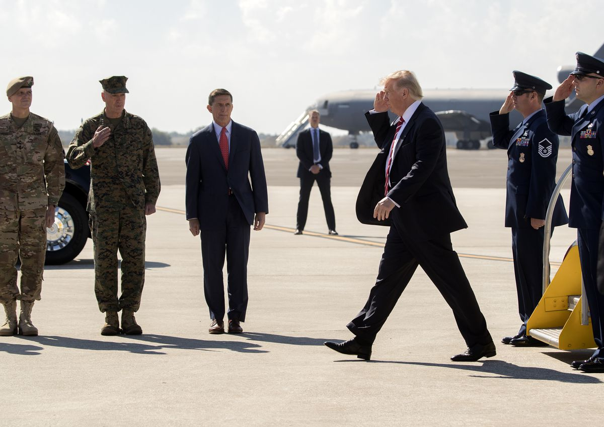 President Donald Trump is greeted by National Security Adviser Michael Flynn and members of the armed forces upon arrival at MacDill Air Force Base in Tampa., Fla., on Monday. (Stephen Crowley/The New York Times)