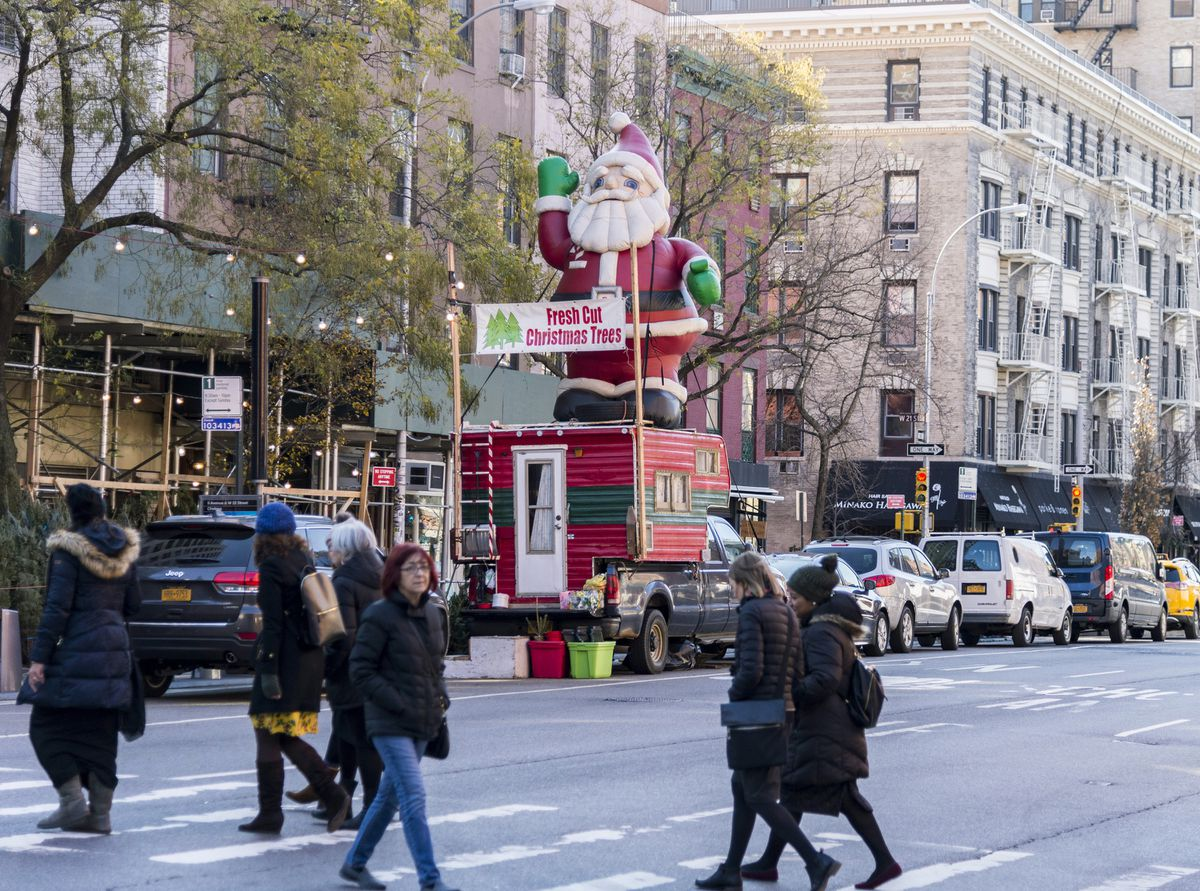 Pedestrians cross 9th Avenue in front of the Gilmartin's Christmas tree stand on Dec. 1, 2017, in New York City. (Taylor Balkom / taylorbalkom.com)