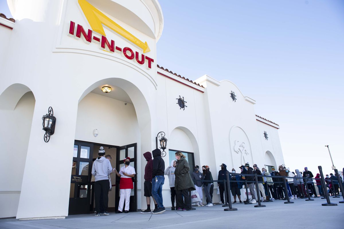 Customers begin to enter the new In-N-Out Burger restaurant Friday morning, Nov. 20, 2020, in northern Colorado Springs, Colo. Customers began waiting in line Tuesday for the opening of the first restaurant in Colorado. A second location opened in Aurora on Friday as well. (Christian Murdock/The Gazette via AP)