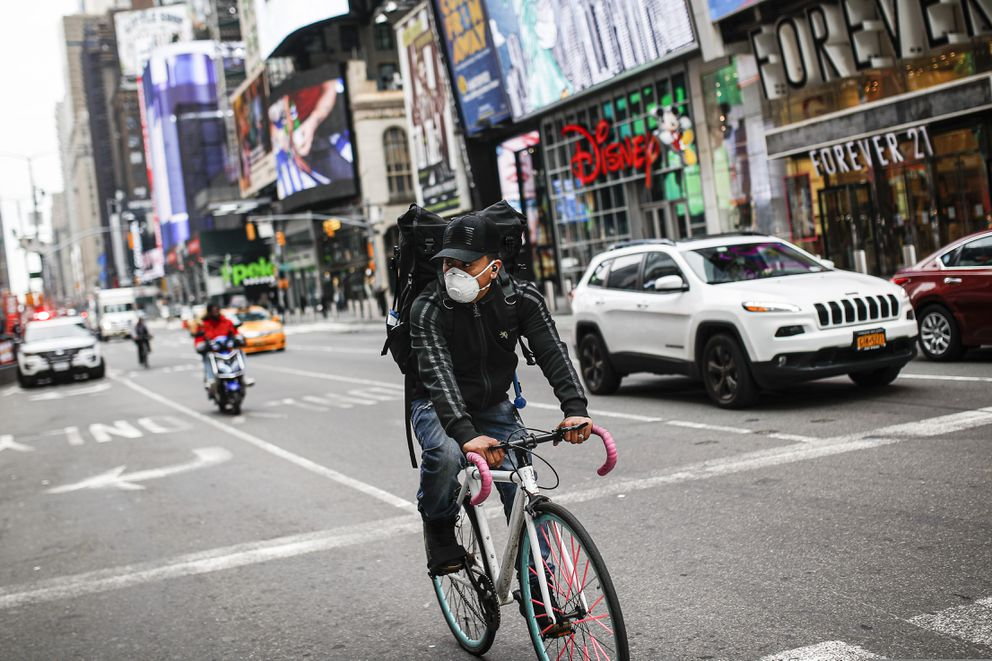A bicycle delivery worker wears a protective face mask as he rides through a sparsely populated Times Square due to COVID-19 concerns, Friday, March 20, 2020, in New York. New York Gov. Andrew Cuomo is ordering all workers in non-essential businesses to stay home and banning gatherings statewide. 'Only essential businesses can have workers commuting to the job or on the job, ' Cuomo said of an executive order he will sign Friday. Nonessential gatherings of individuals of any size or for any reason are canceled or postponed. (AP Photo/John Minchillo)