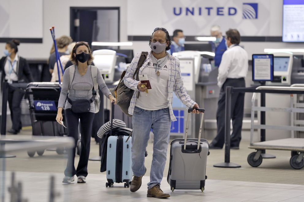 Passengers wearing personal protective face masks leave the United Airline ticket counter after checking in Tuesday, June 16, 2020, at the Tampa International Airport in Tampa, Fla. (AP Photo/Chris O'Meara)