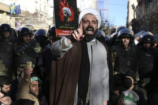 Surrounded by policemen, a Muslim cleric addresses a crowd during a demonstration to protest the execution of Saudi Shiite Sheikh Nimr al-Nimr, shown in the poster in background, in front of the Saudi embassy in Tehran, Iran, Sunday, Jan. 3, 2016. Saudi Arabia announced the execution of al-Nimr on Saturday along with 46 others. Al-Nimr was a central figure in protests by Saudi Arabia's Shiite minority until his arrest in 2012, and his execution drew condemnation from Shiites across the region.