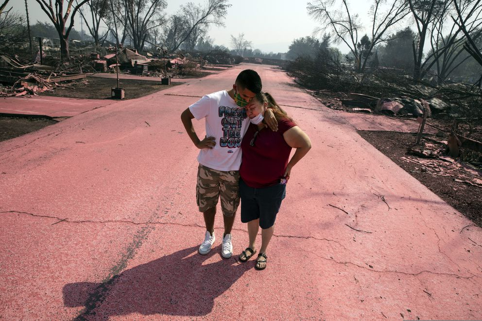 Maria Centeno, right, from Mexico, is consoled by her neighbor Hector Rocha after seeing their destroyed mobile homes at the Talent Mobile Estates, Thursday, Sept. 10, 2020, in Talent, Ore., after as wildfires devastate the region. (AP Photo/Paula Bronstein)
