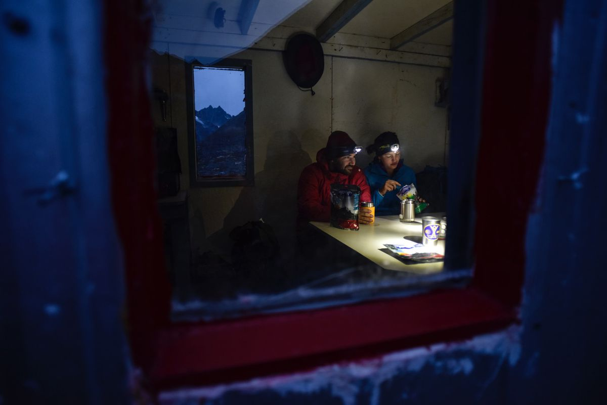 Kyle Miller, left, and Tess Forstner, both of Palmer, hunker down for a hot meal in the Dnigi Hut after a long day hiking from the Bomber Hut in the Talkeetna Mountains last September. The pair were on a five-day trek from Archangel Valley to the trailhead at Eska Falls, a trip of about 50 miles. (Photo by Matt Hage)