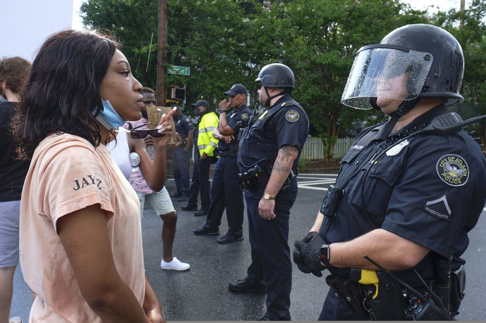 Protesters stand in front of police Sunday, June 14, 2020, in Atlanta. Rayshard Brooks, 27, was fatally shot by an Atlanta police officer Friday night. (Ben Gray/Atlanta Journal-Constitution via AP)