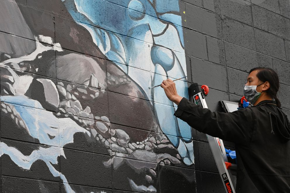 UAA art professor Tom Chung work on 'Ice Cave in Juneau, ' part of a climate change mural being painted on the SEED Lab in downtown Anchorage on Tuesday, Sept. 22, 2020. (Bill Roth / ADN)