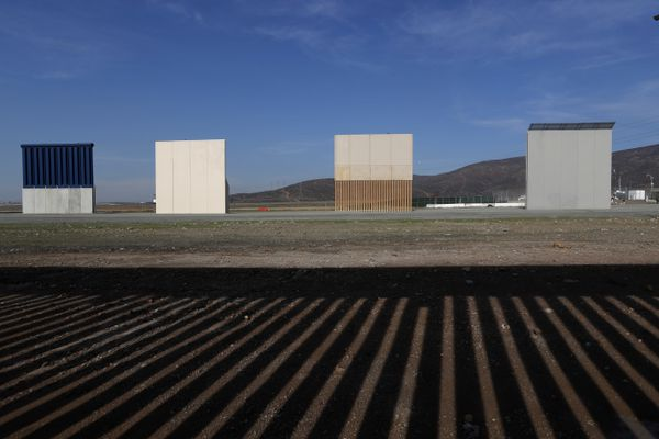 FILE - In this Wednesday, Dec. 12, 2018, file photo, border wall prototypes stand in San Diego near the Mexico-U.S. border, seen from Tijuana, Mexico, where the current wall casts a shadow in the foreground. (AP Photo/Moises Castillo, File)