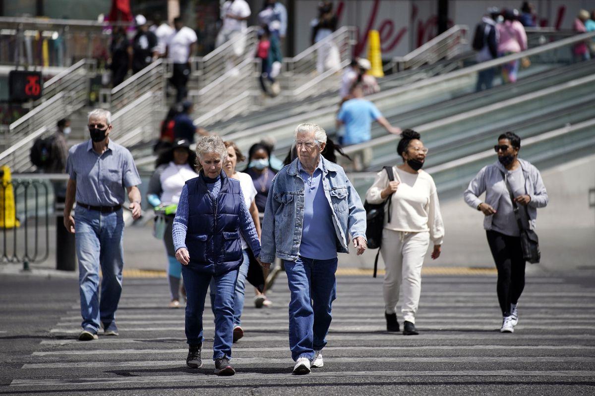 In this Tuesday, April 27, 2021, file photo, masked and unmasked pedestrians walk across Las Vegas Boulevard, in Las Vegas. (AP Photo/John Locher, File)