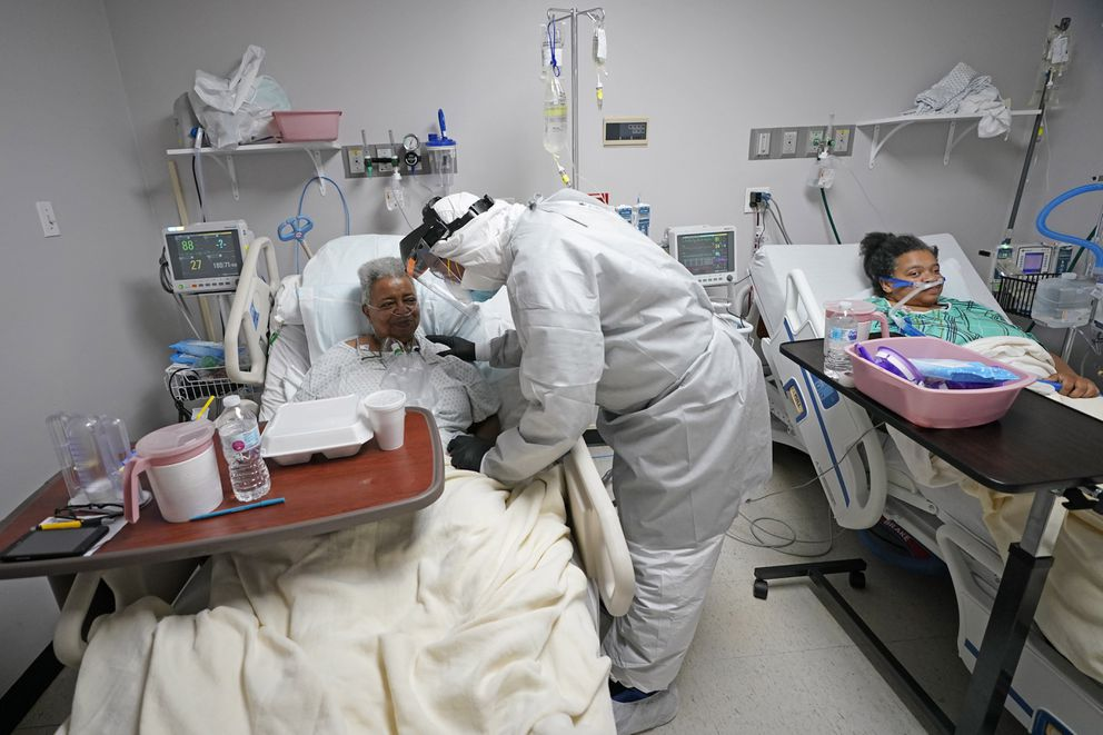 Dr. Joseph Varon, center, visits with Dorothy Webb, left, and her daughter, Tammie, while making his rounds inside the Coronavirus Unit at United Memorial Medical Center, Monday, July 6, 2020, in Houston. (AP Photo/David J. Phillip)