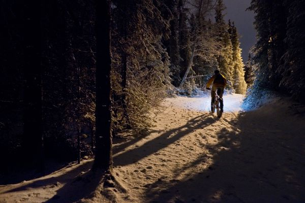 A cyclist rides over new snow on the Tour of Anchorage Trail near Service High School on Dec. 19, 2017. (Marc Lester/ ADN)