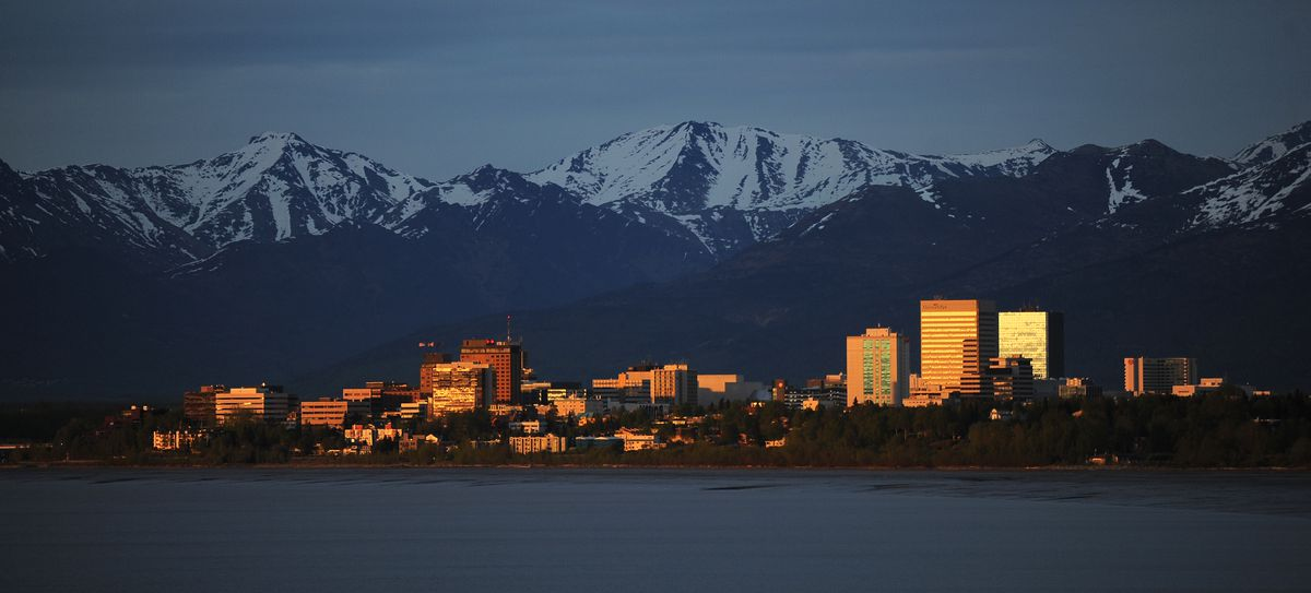 The setting sun lights up the buildings of downtown Anchorage beneath the Chugach Mountains as seen from Port Woronzof in West Anchorage on May 22, 2018. (Bob Hallinen / ADN)