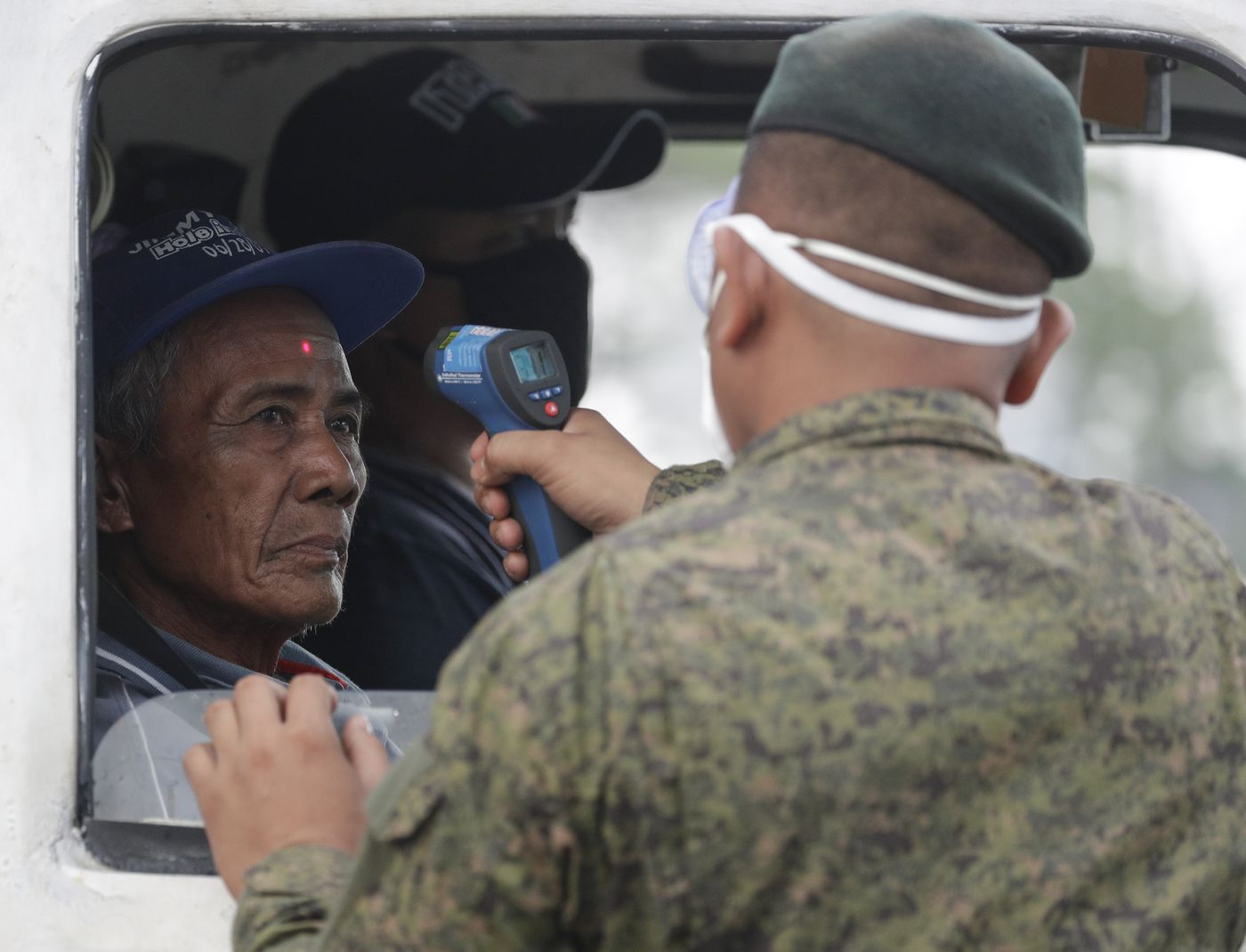 A man's temperature is checked by an army trooper before entering the metropolis at a checkpoint on the outskirts of Quezon city, Philippines Sunday, March 15, 2020. Thousands of Philippine police, backed by the army and coast guard, have started sealing the densely populated capital from most domestic travelers in one of Southeast Asia's most drastic containment moves against the coronavirus. (AP Photo/Aaron Favila)