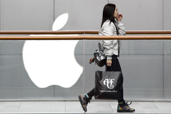 A woman carries a paper bag containing goods purchased from American brand Abercrombie & Fitch walks past an Apple store at the capital city's popular shopping mall in Beijing, Tuesday, Feb. 26, 2019. American companies in China increasingly worry U.S.-Chinese relations will deteriorate and are
