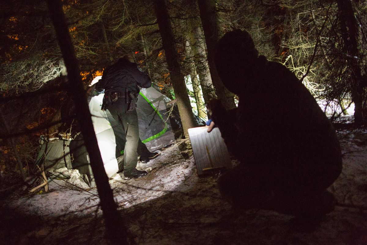 Air Force Staff Sgt. Al Kim waits for Anchorage policeman Mark Karstetter to make contact with a homeless person camped along Chester Creek before interviewing him during the annual homeless count on Jan. 27, 2016. (Loren Holmes / ADN)
