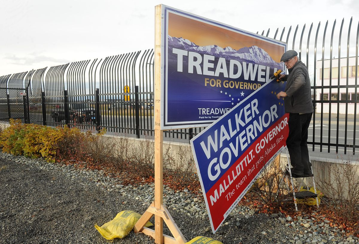 Bob Walker, the older brother ofGov. Bill Walker, takes down Walker campaign signs at Merrill Field in Anchorage on Saturday, Oct 20, 2018. The Walker campaign had taken over the Mead Treadwell sign stand after Treadwell ended his campaign for governor. Walker also removed the Treadwell signs. (Bob Hallinen / ADN)