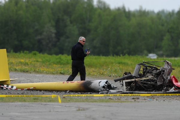 NTSB investigator Clint Johnson photographs the scene of a Robinson R44 helicopter crash that killed pilot Tom Moore, 62 of Anchorage, at Birchwood Airport on Wednesday, May 28, 2014. (Bill Roth / ADN archive 2014)
