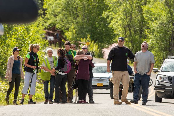 Mike Roberts, at right in black, comforts Sean Rheault after they learned that their friend Mike Soltis' body was found mauled by a bear Wednesday morning, June 20, 2018 along Hiland Road in Eagle River. Roberts and Rheault were co-workers and friends of Soltis'. (Loren Holmes / ADN)