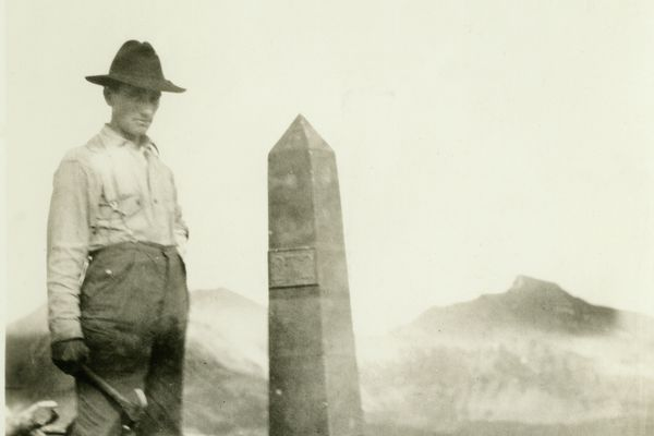 A man working with the International Boundary Commission in the early 1900s poses next to one of more than 200 obelisks that line the Alaska/Canada border. (NOAA Photo Library)