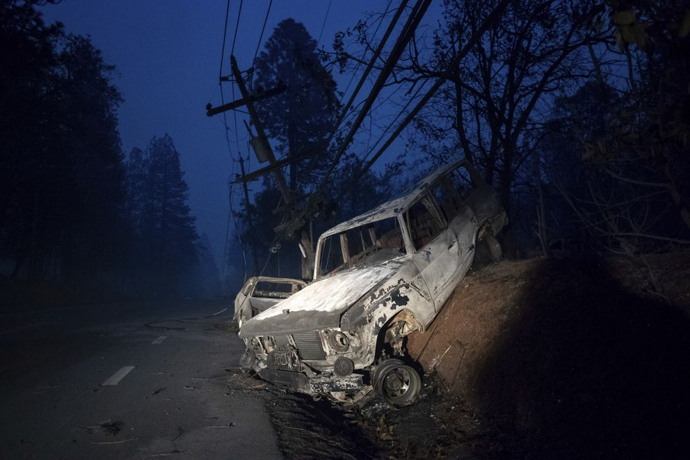 A scorched vehicle rests on a roadside as the Camp Fire tears through Paradise, Calif., on Thursday, Nov. 8, 2018. Tens of thousands of people fled a fast-moving wildfire Thursday in Northern California, some clutching babies and pets as they abandoned vehicles and struck out on foot ahead of the flames that forced the evacuation of an entire town and destroyed hundreds of structures. (AP Photo/Noah Berger)