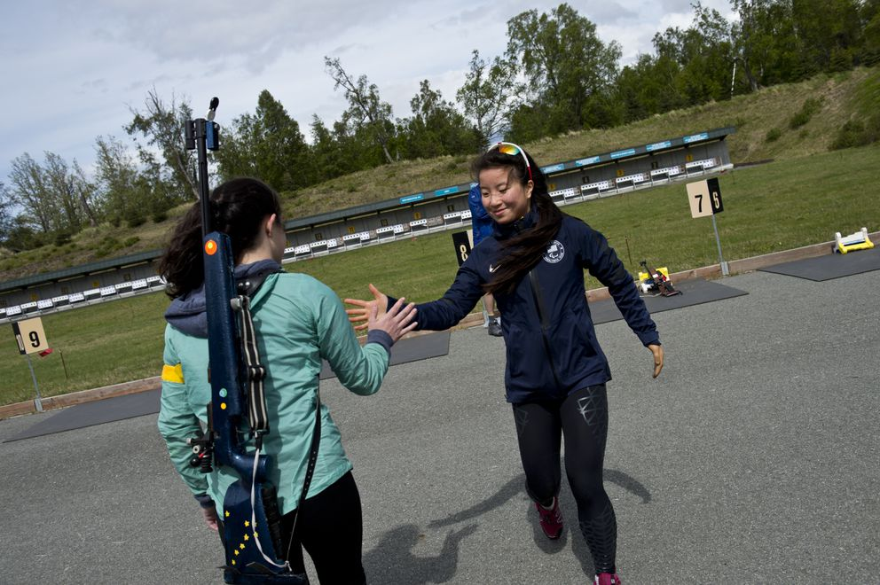 Mia Rossi, left, high-fives Grace Miller during a drill. Miller, a Team USA Paralympian in cross-country skiing, was getting her first day of instruction in biathlon, she said. (Marc Lester / Anchorage Daily News)