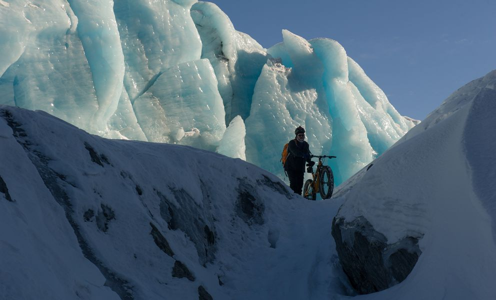 Biker Sean Ruddy pushes his bike along a narrow passage in the toe of Knik Glacier, March 17, 2017. (Michael Dinneen / Micheal Dinneen Photography)